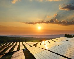 Sunset over photovoltaic panels of solar power station in the countryside. View from above.